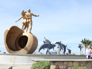 Sculpture of two humans striding along behind pod of leaping dolphins