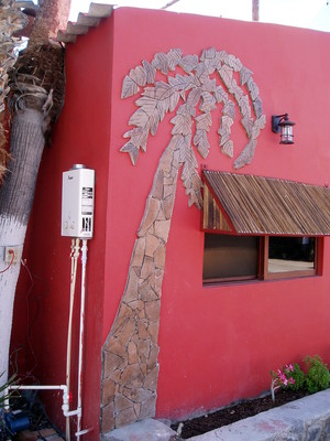 Mosaic of palm tree created in rock on wall of house in Posada Concepcion