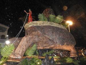 Woman perched on giant tortoise parade float