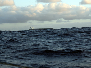 Freighter partly hidden by swell