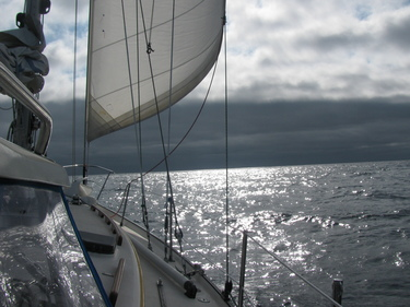 Passing from sunny seas under darker clouds