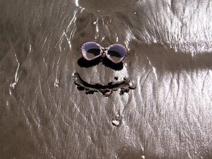 Smiley face scribed in sand with shell eyes